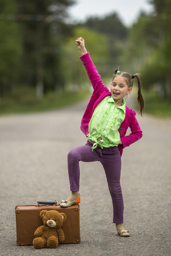 Ljus liten flicka på vägen med en resväska och en nallebjörn royaltyfri foto