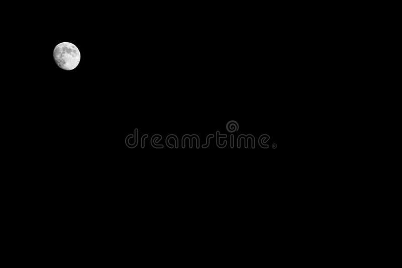 Ljus liten full vit måne på en svart himmel på natten, bakgrund, kopieringsutrymme royaltyfria bilder