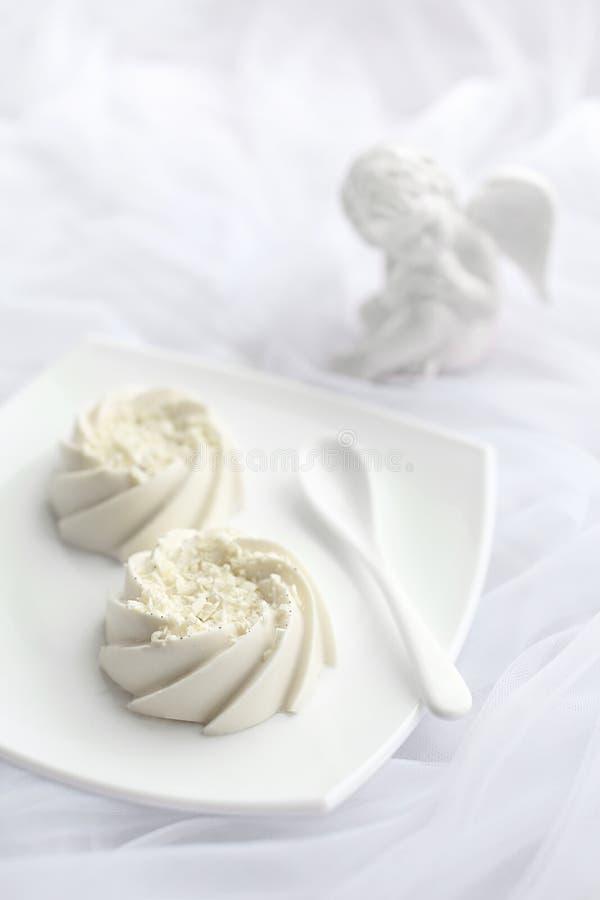 Ljus luftig efterrätt på den vita keramiska plattan i monokrom arkivfoton