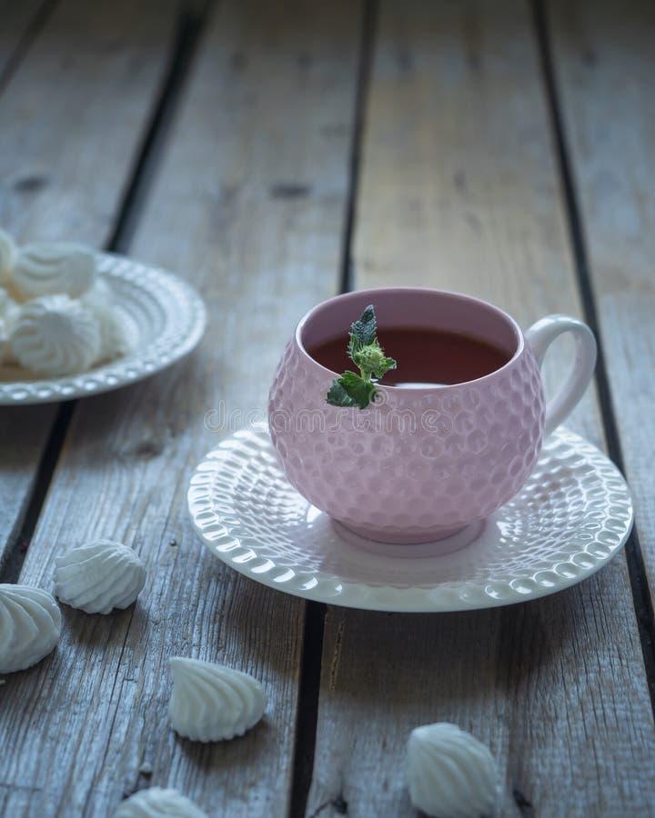 Ljus lunch med te och kakor i elegant keramisk disk och en tesked, sammansättningen på den omålade tabellen för lantligt bräde, arkivbild