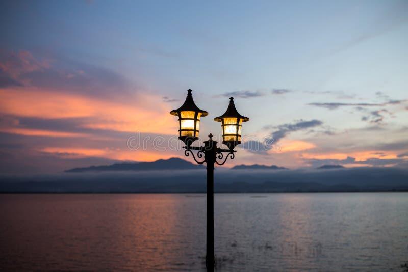 Ljus lykta i bergbakgrunds- och skymningmörker efter den atmosfäriska solnedgångtidromantiker arkivfoto