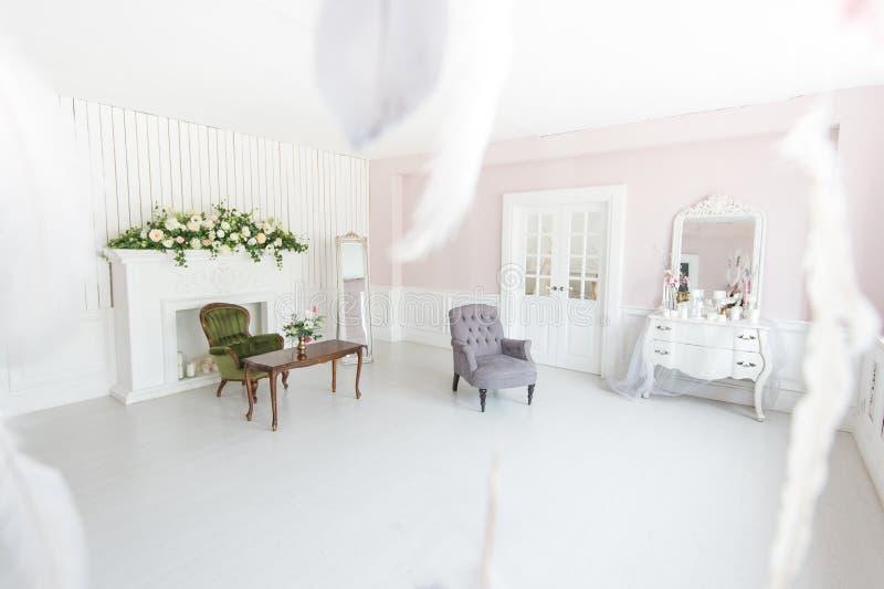 Ljus lyxig inre av vardagsrummet med spisen och fåtöljer som dekoreras med blommor arkivfoto