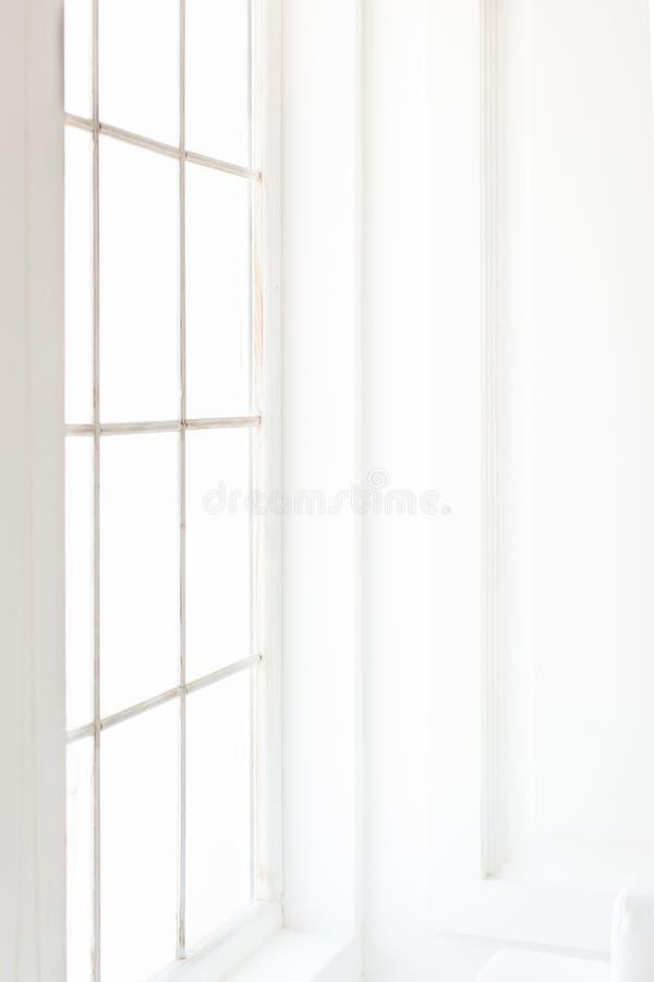 Ljus minimalist lakonisk inre med vita väggar, stort fönster fotografering för bildbyråer