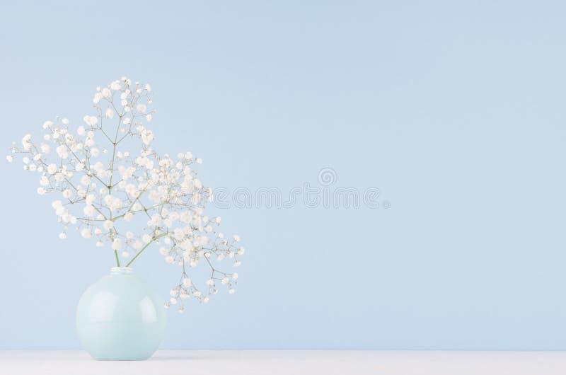 Ljus mjuk elegant hem- dekor med små luftiga blommor i glansig pastellfärgad blå vas på trätabellen och den blåa väggen royaltyfri fotografi