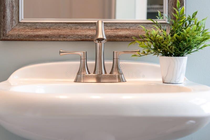 Ljus och ljus closeup av badrumvasken med den borstade myntvattenkranen arkivfoton