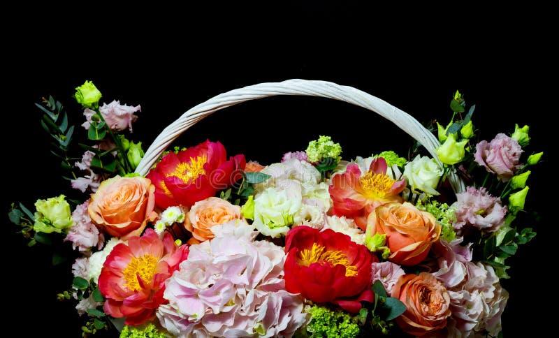 Ljus ordning för vit blomma i en korg på en mörk bakgrund royaltyfri bild