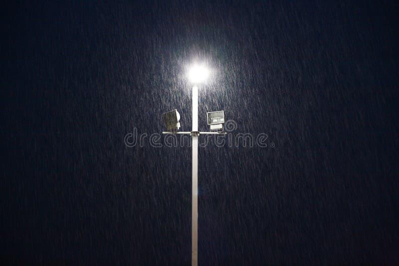 Ljus på ett sportfält på aftonen i regnet royaltyfri bild