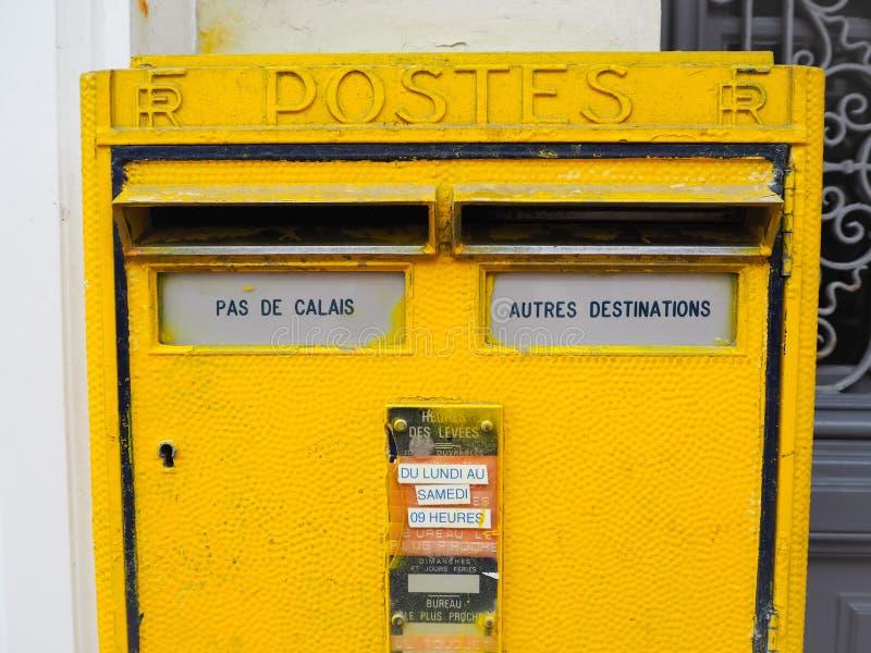 Ljus postbox för gul metall från den franska National Post med ett hängivet rum för Pas royaltyfria bilder