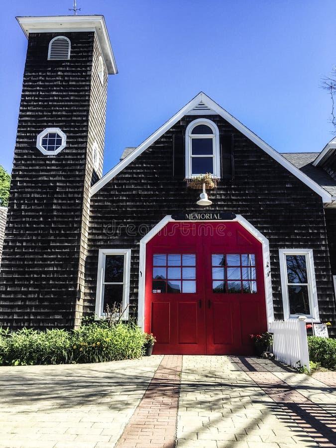 Ljus röd dörr på en gammal brandstation i Jamestown RI royaltyfri fotografi