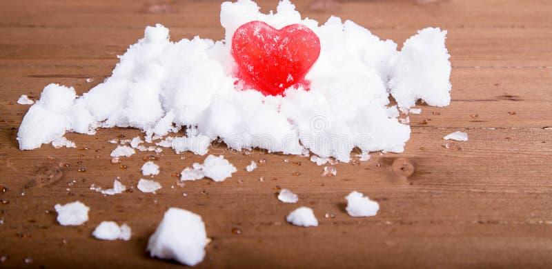 Ljus röd ishjärta på en kulle av vit snö royaltyfri foto
