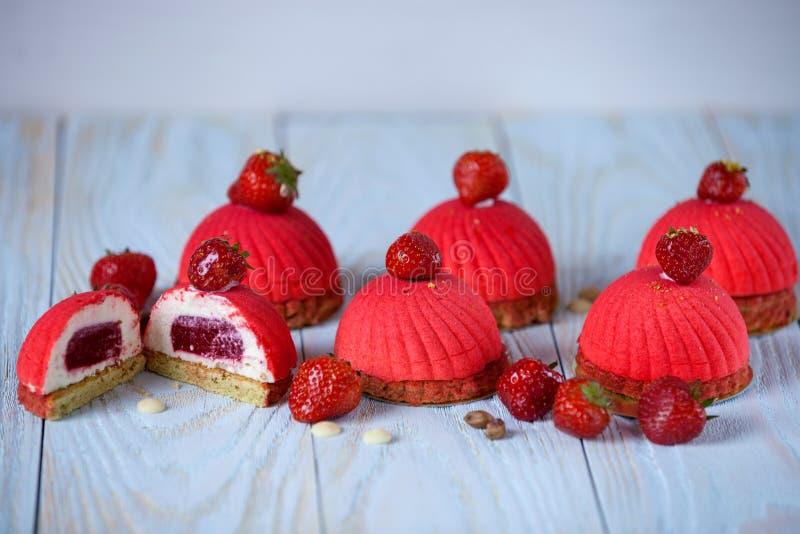 Ljus röd moussekaka med jordgubbegarnering på en blå träbakgrund royaltyfri bild