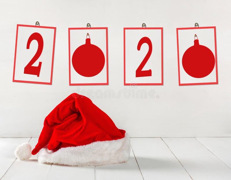 Ljus röd Santa Claus hatt med pappers- ramar och numret 2020 arkivbild