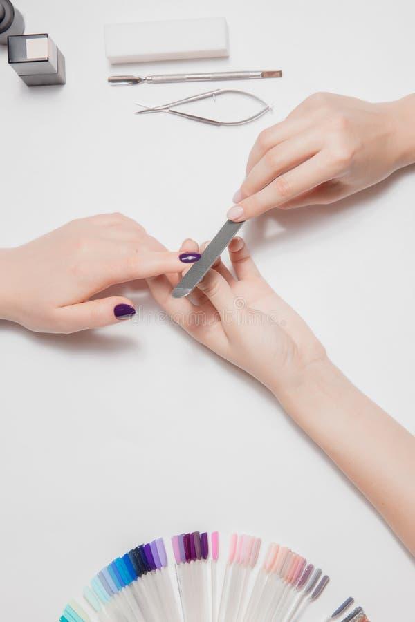 Ljus ram kvinnlign hands manicurebehandling Att spara spikar med speciala hjälpmedel Lilafernissa arkivbilder