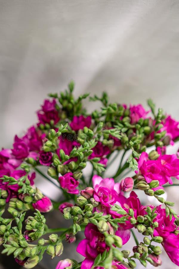 Ljus rosa freesia blommar i den glass vasen på trätabellen Härlig sommarbukett Ordning med blandningblommor _ royaltyfri fotografi