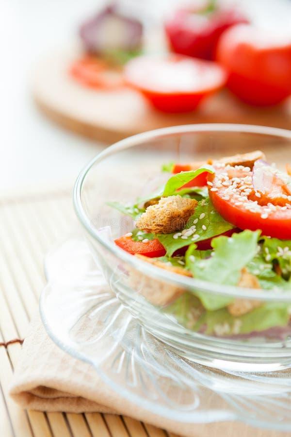 Ljus sallad med krutonger och tomater arkivfoto