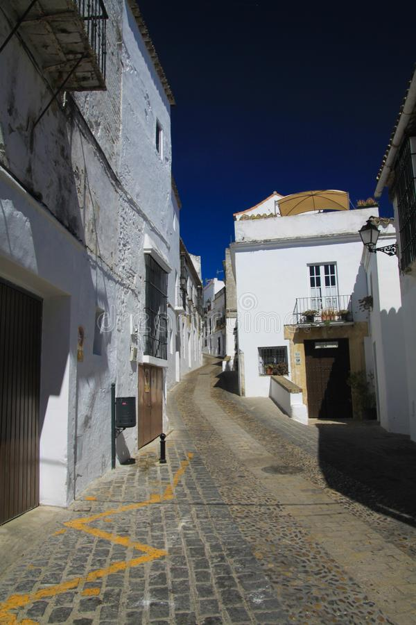 Ljus skinande isoalated tom smal gränd med kullersten mot djupblå himmel och typiska spanska vita hus - Arcos de la royaltyfri foto