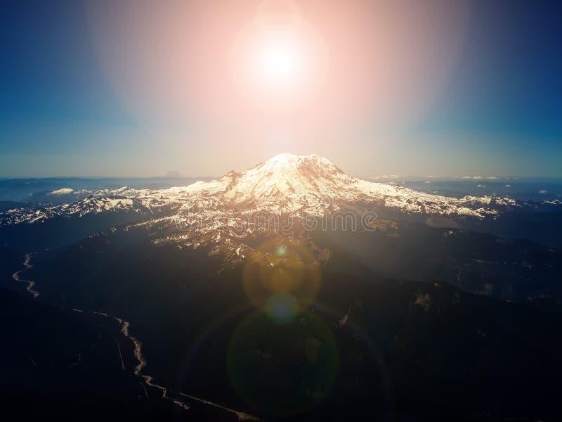 Ljus sol i himmel ovanför bergmaximumet - flyg- över huvudet sikt royaltyfria foton