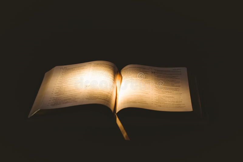 Ljus som skiner på den öppna bibeln arkivbilder