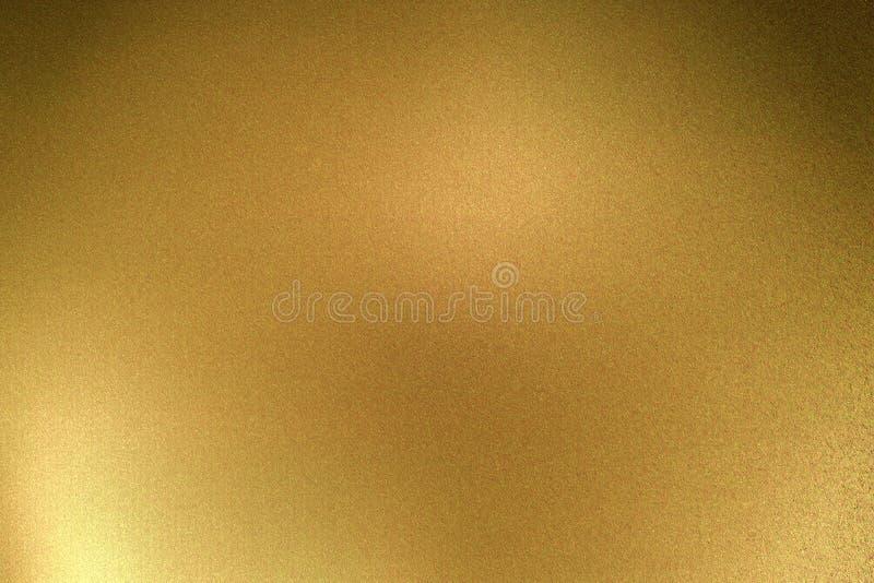 Ljus som skiner på den guld- metalliska plattan i mörkt rum, abstrakt texturbakgrund arkivfoton