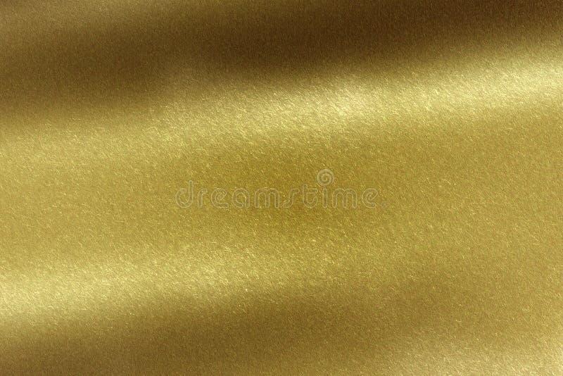 Ljus som skiner på det borstade guld- metallarket, abstrakt texturbakgrund arkivfoton