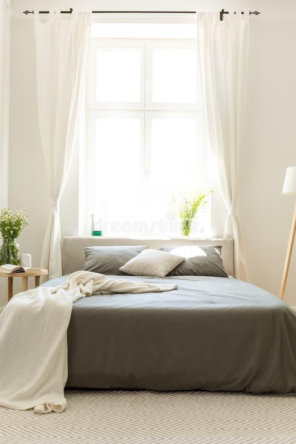 Ljus sovruminre med ett iklätt mörker för säng - grå sängkläder som placeras mot en vit vägg med ett stort fönster Verkligt foto royaltyfri fotografi