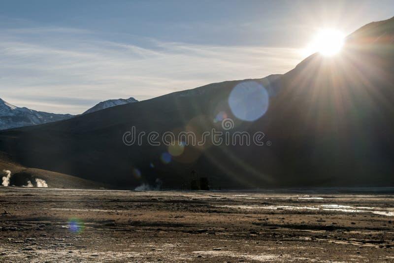 Ljus stigningssol ovanför att få utbrott den varma geyseren av ånga i Geysersfältet för El Tatio på ottasoluppgång, Atacama öken, fotografering för bildbyråer
