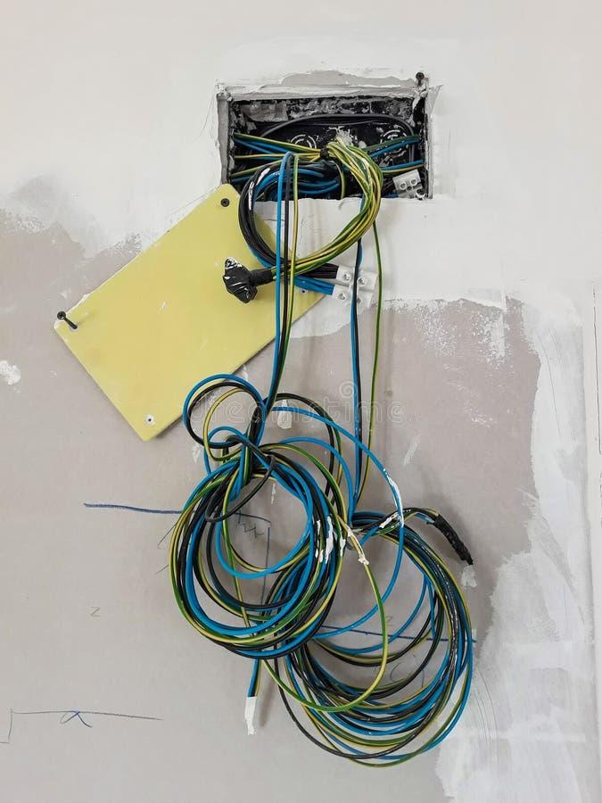 Ljus strömbrytare med ingen platta på väggen för renovering med kablar som hänger för installation arkivfoto