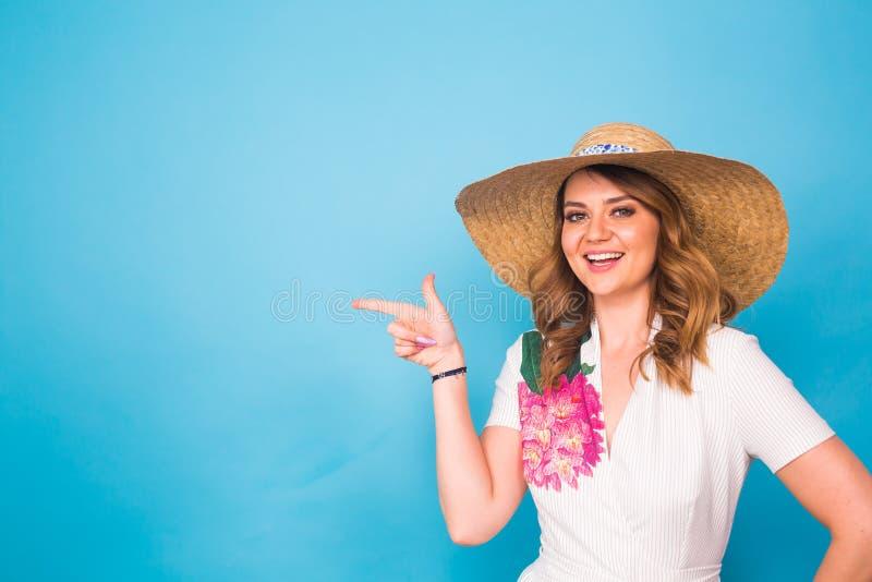 Ljus studiostående av den attraktiva unga kvinnan som pekar copyspace på blå bakgrund arkivbilder