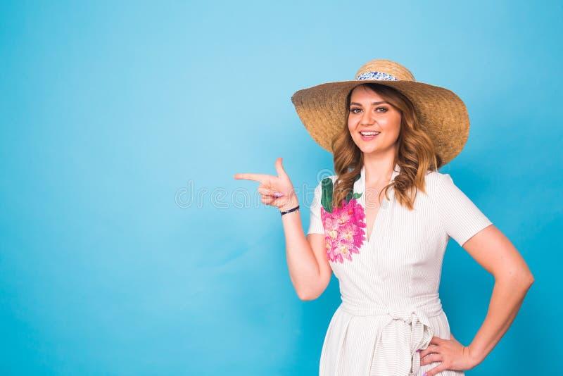 Ljus studiostående av den attraktiva unga kvinnan som pekar copyspace på blå bakgrund royaltyfri bild