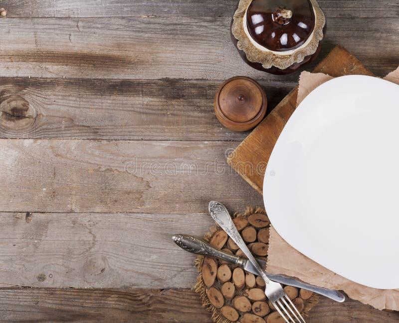 Ljus tom platta med köktillbehör på en träbakgrund i tappningstil ovanf?r sikt arkivfoto