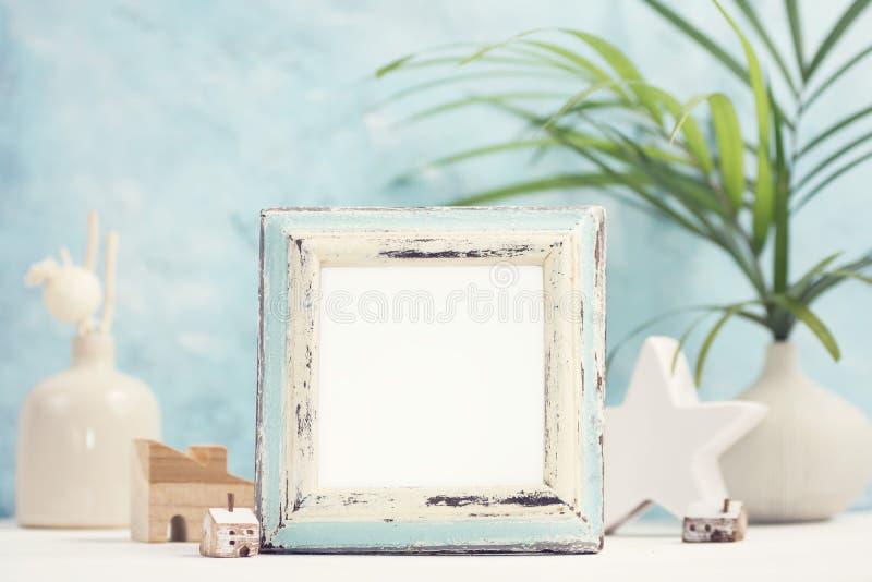Ljus tropisk åtlöje upp med ramen för tappningvit- och blåttfoto, palmblad i vas och den hem- dekoren mot den blåa väggen royaltyfri fotografi