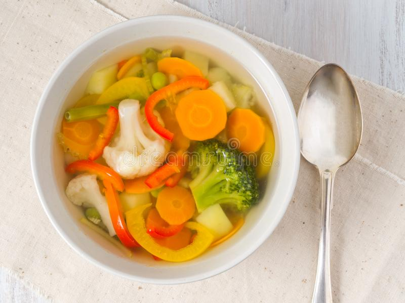 Ljus vårgrönsaksoppa med blomkålen, broccoli, peppar, morot, gröna ärtor Bästa sikt, vit träbakgrund royaltyfri foto