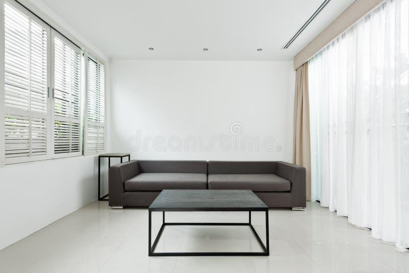 Ljus vardagsrum med den gråa soffan arkivfoton