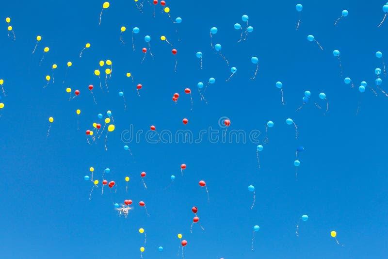 Ljusa blåa, röda och gula luftballonger att stiga upp i den blåa himlen framförd bollillustration för bakgrund 3d royaltyfri foto