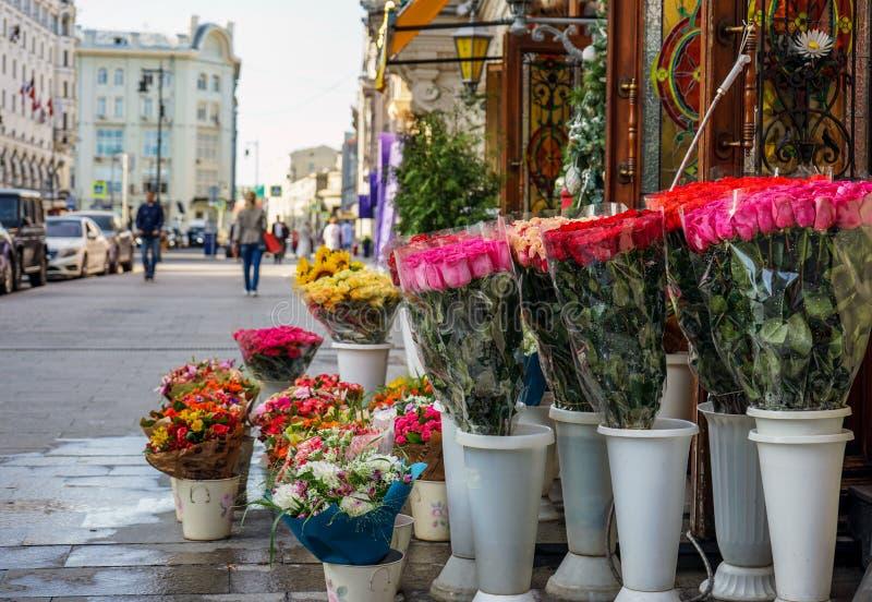 Ljusa buketter av blommor är på gatan nära blomsterhandeln royaltyfri bild