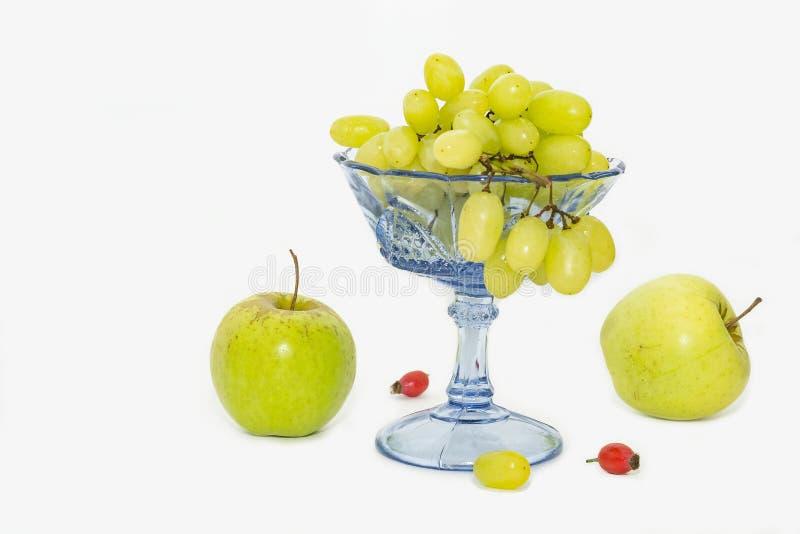Ljusa druvor i en vas- och äppleserie royaltyfri foto