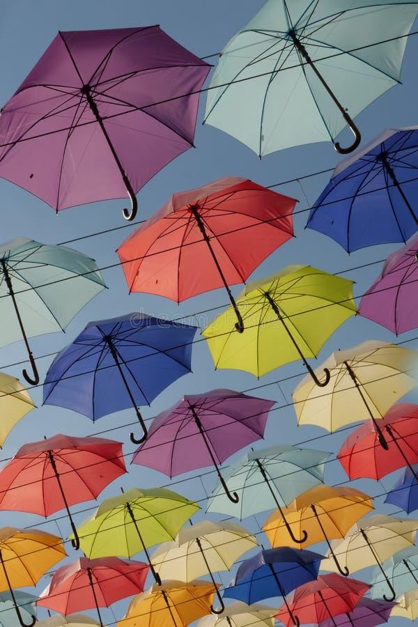Ljusa färgglade paraplyer som hänger på bakgrunden för blå himmel för kablar arkivbilder