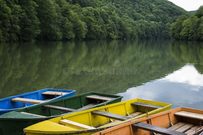 Ljusa färgrika fartyg förtöjde på den tysta bergsjön fotografering för bildbyråer