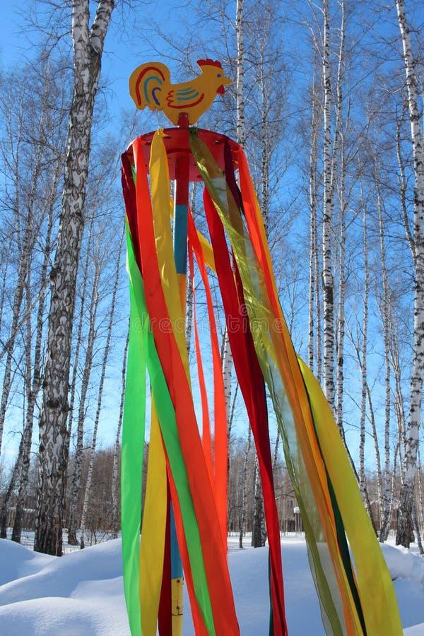 Ljusa flödande band på polen i den traditionella garneringen för trän av forntida Ryssland i festmåltiden av karnevalet på våren, fotografering för bildbyråer