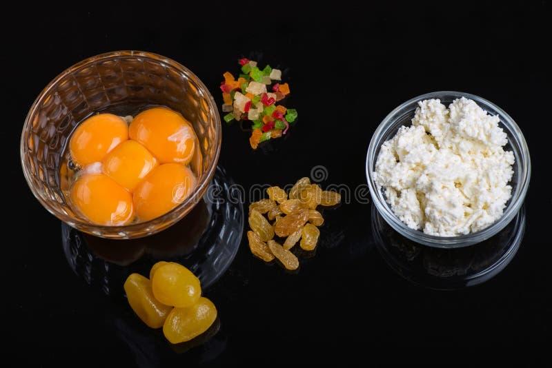 Ljusa gula ?ggulor i en exponeringsglasbunke p? svart bakgrund Ingredienser för att laga mat läcker disk royaltyfri foto