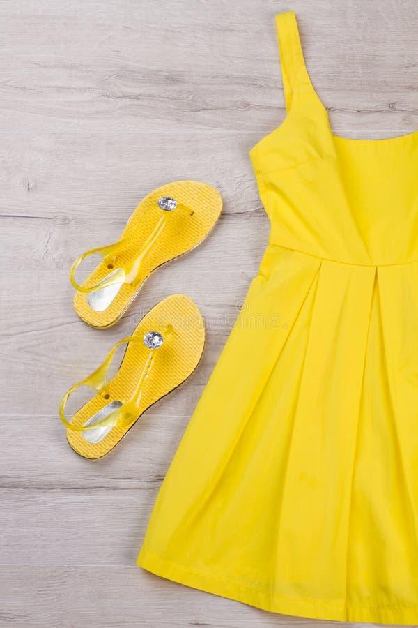 Ljusa gula klänning och sandaler på en ljus bakgrund arkivfoton