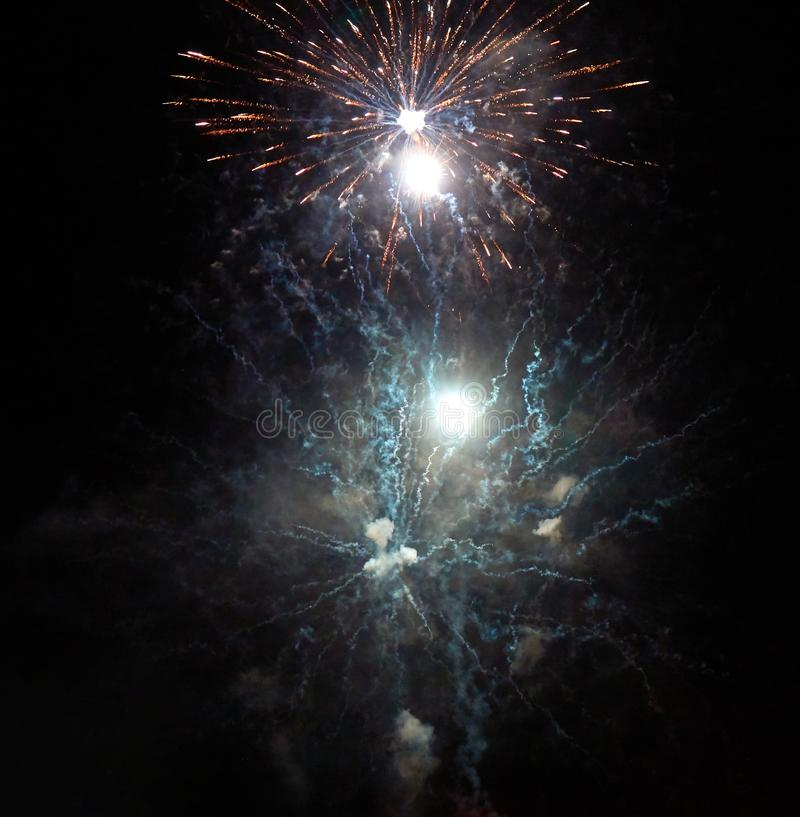 Ljusa guld- fyrverkerier, rök och de ljusa ljusblixtarna i natthimlen royaltyfria foton