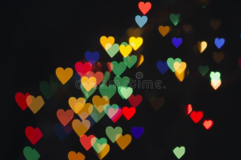 Ljusa hjärtor på en mörk bakgrund royaltyfria foton