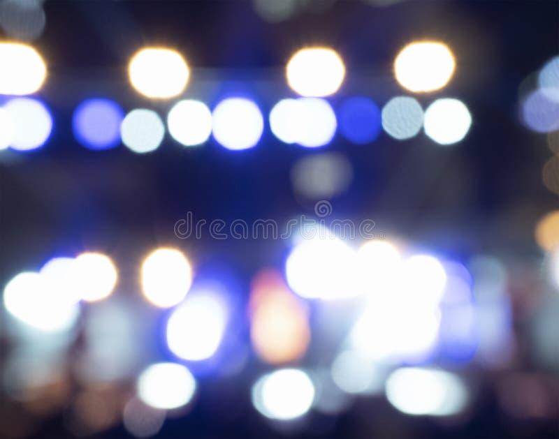 Ljusa ljus av platsen på den musikaliska presentationen i aftonen suddighet bakgrund royaltyfri fotografi