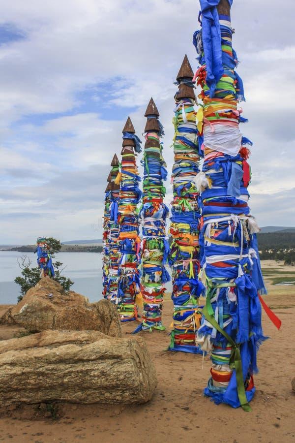 Ljusa mångfärgade band som binds till pelare på ön av Olkhon på Lake Baikal royaltyfria foton