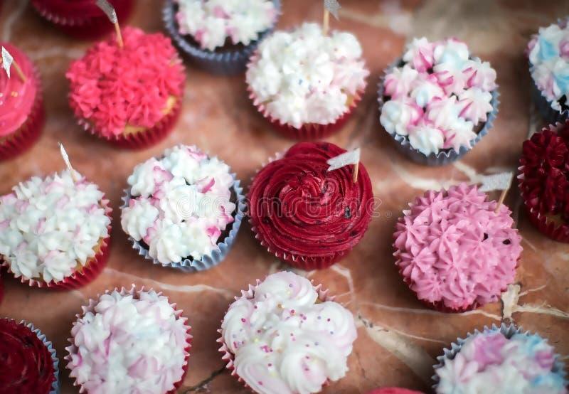 Ljusa muffin med rosa och vit glasyr på kaka på en bankett arkivbild