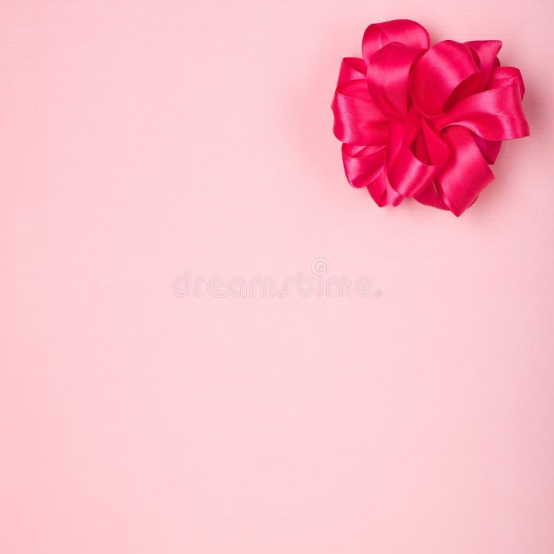 Ljusa nästan röda rosa färger, satängpilbåge i övresidohörn av ljusa Rose Pink Fabric Background med rum eller utrymme i mitten f royaltyfri foto