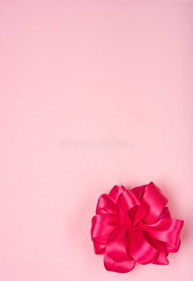 Ljusa nästan röda rosa färger, satängpilbåge i lägre sidohörn av ljusa Rose Pink Fabric Background med rum eller utrymme i mitten arkivbild