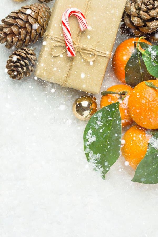Ljusa orange tangerin på filialer med den gröna sidagåvaasken i rotting för hantverkpappersgodis sörjer kottar i snö nytt år för  royaltyfria bilder
