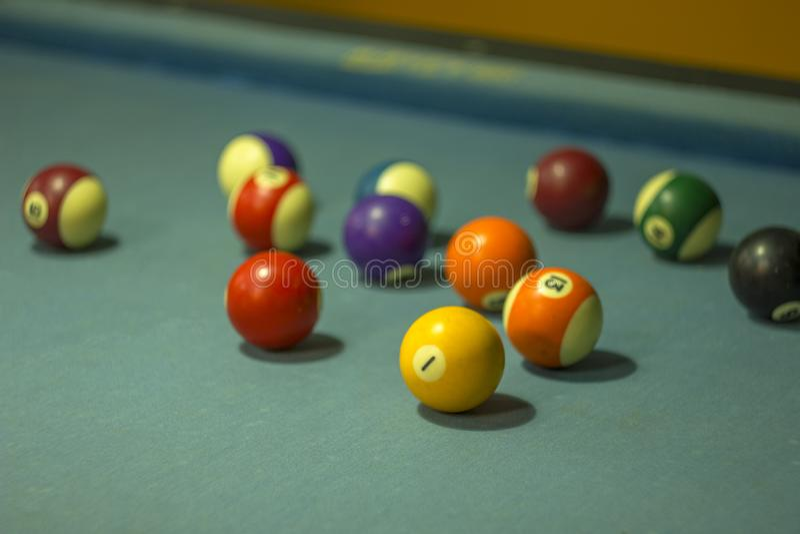 Ljusa oskarpa gamla sjaskiga mång--färgade billiardbollar på den blåa torkduken arkivfoto